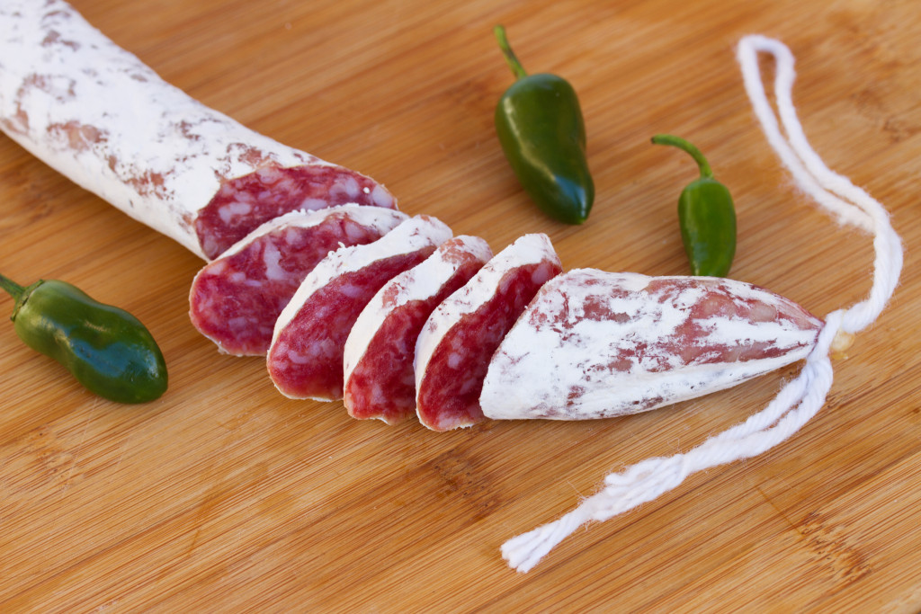 Spanish  fuet sausages with green peppers on wooden table